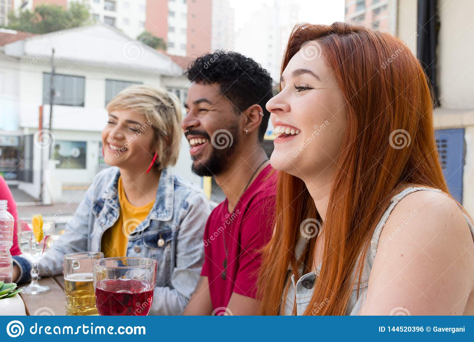 Cheerful young friends cheering and drinking together at cafe bar outdoor. Spring, warm, togetherness, lifestyle, diversity