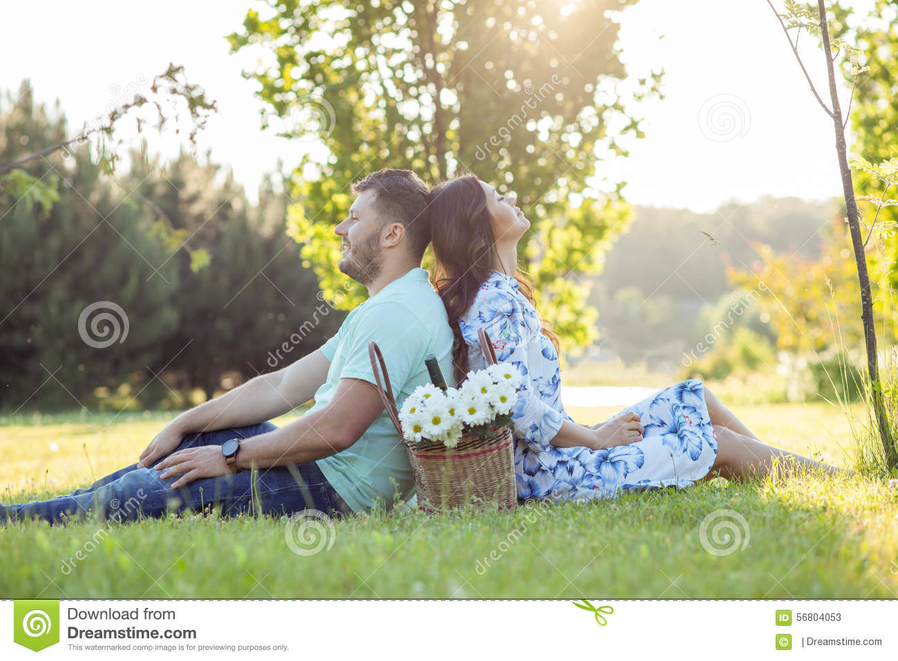 Cheerful young loving couple is relaxing in park