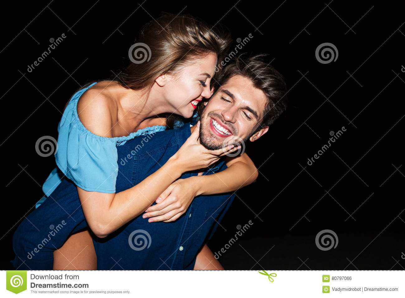 Cheerful young man holding girlfriend on his back at night