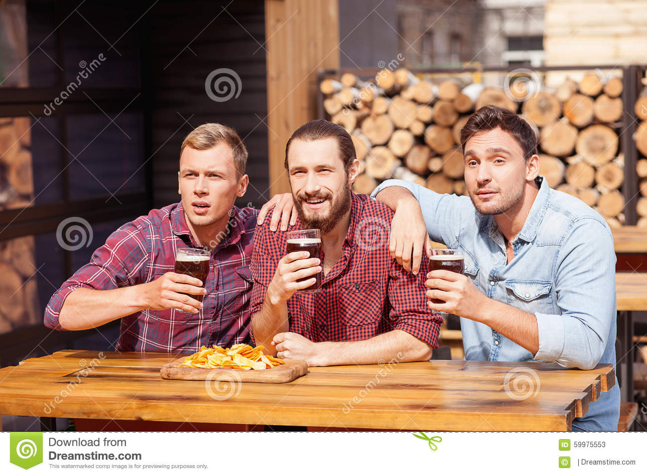 Cheerful young men are watching game in pub stock image for Food bar drinking game
