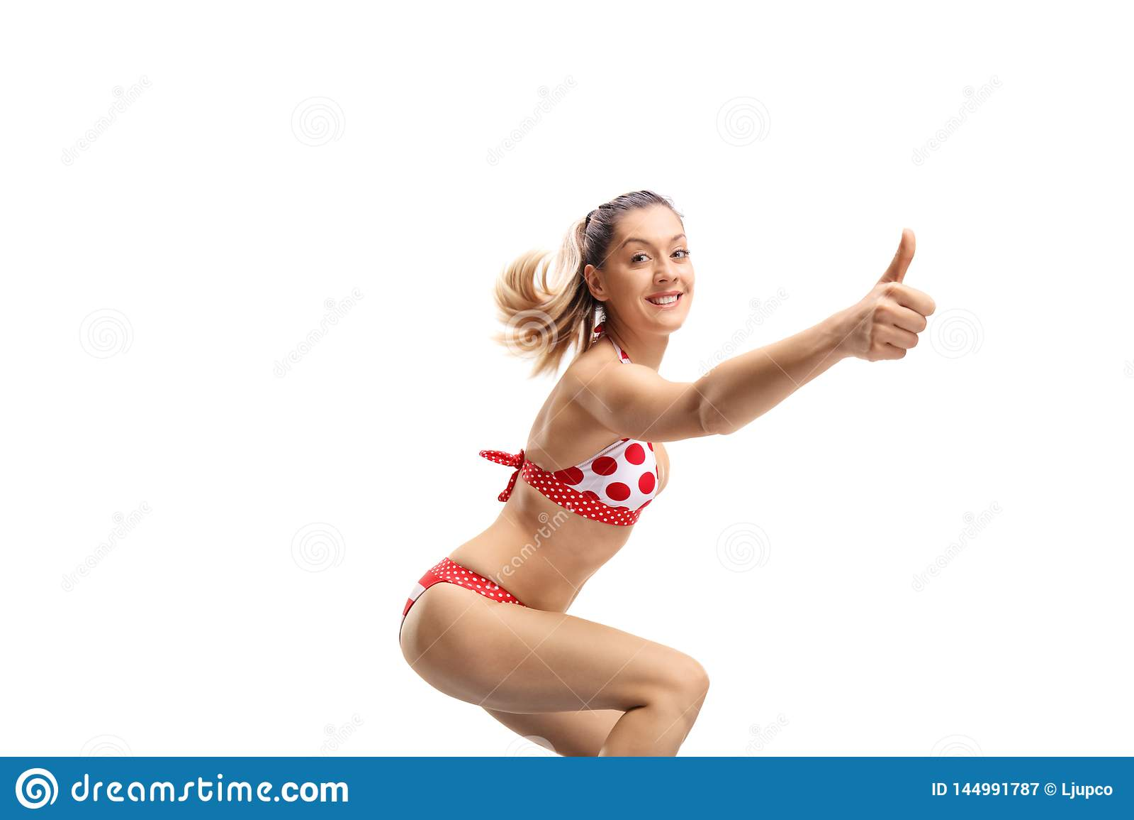 Cheerful young woman in bikini making a thumb up gesture