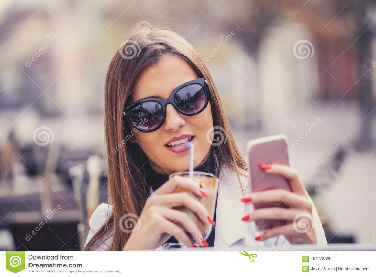Cheerful young woman holding smart phone and drinking hot choco