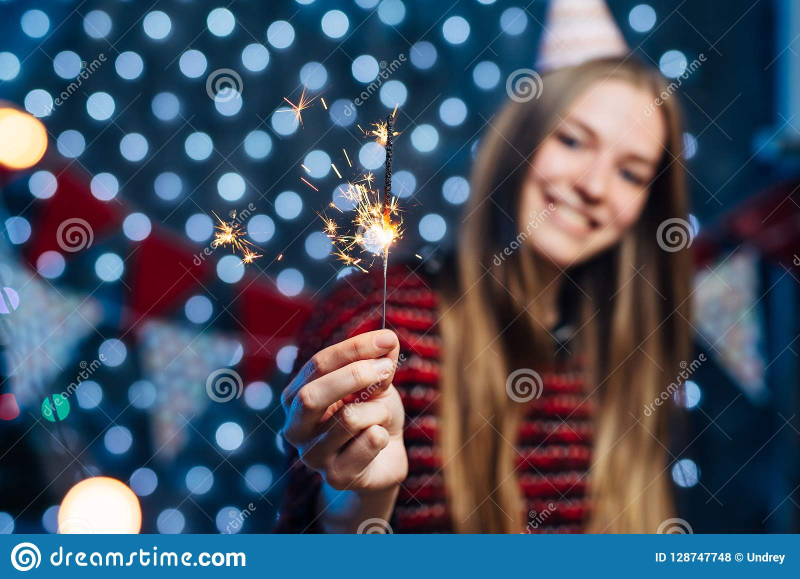 Cheerful young woman holding sparkler in hand. Christmas New Year