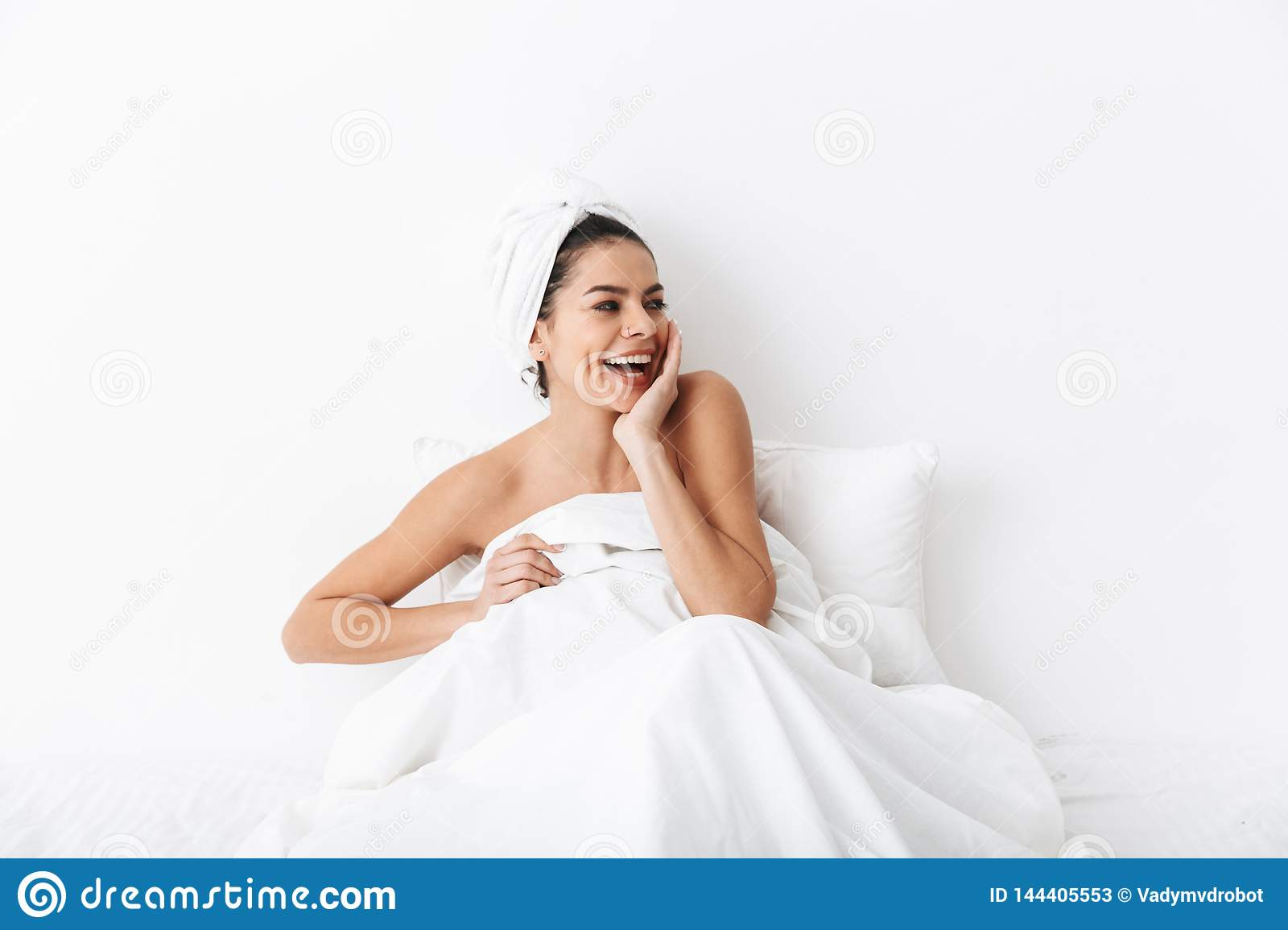 Cheerful young woman sitting in bed after shower