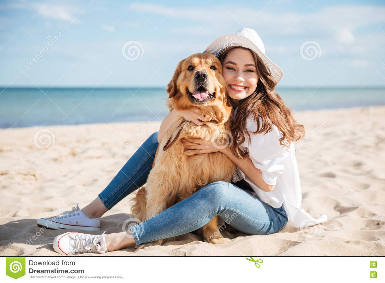 Cheerful young woman sitting and hugging her dog on beach