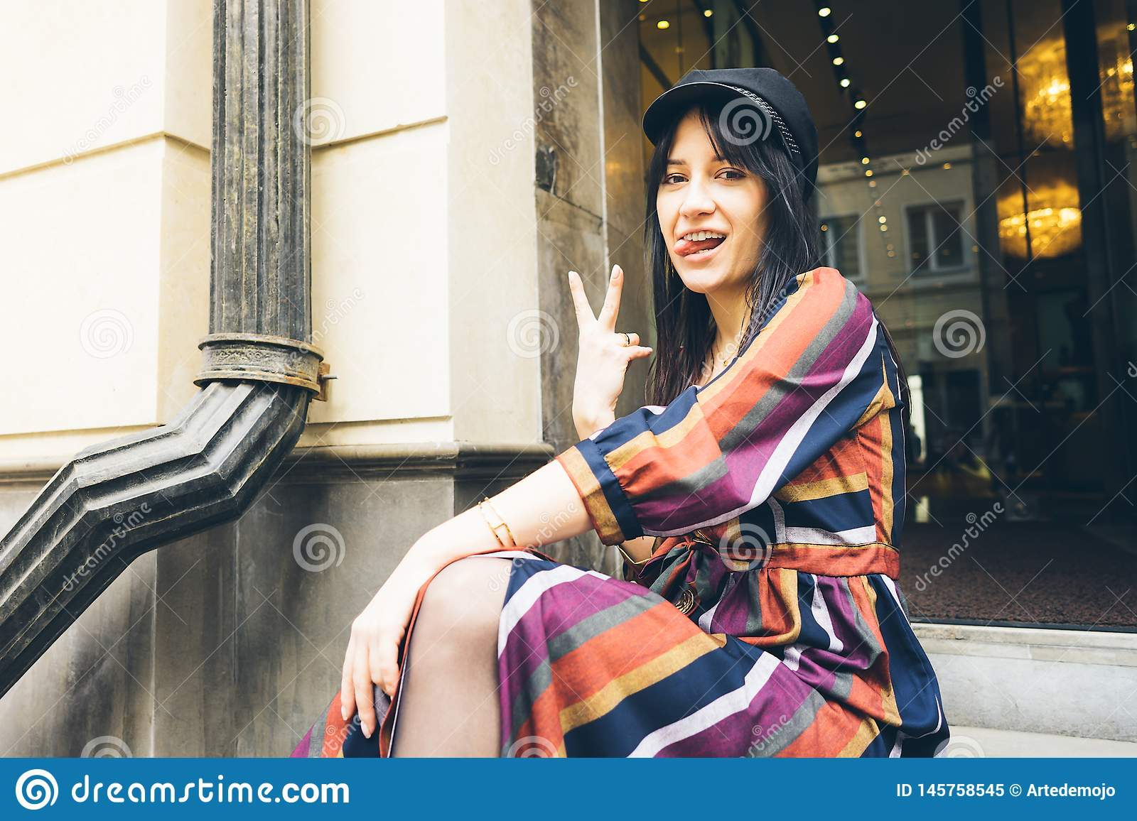 Cheerful young woman is sitting on the steps of a boutique showing tongue