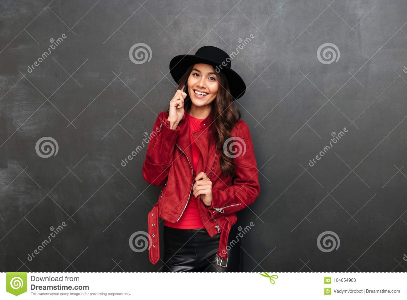 9d62c3f8c4ba8 Photo of cheerful young woman wearing hat standing over dark grey wall  chalkboard talking by mobile phone. Looking camera.