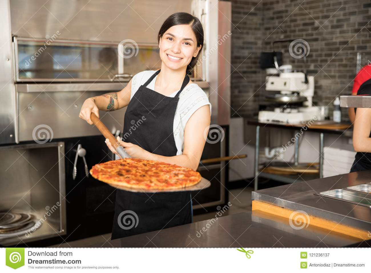 Smiling chef holding big shovel with pizza