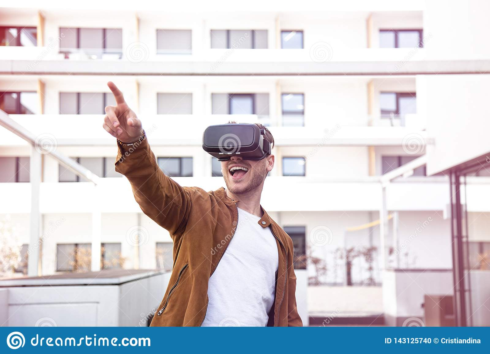 Cheerfully Jonge Volwassen Charmante Mens die Virtuele de Werkelijkheidsglazen gebruikt van VR Openlucht