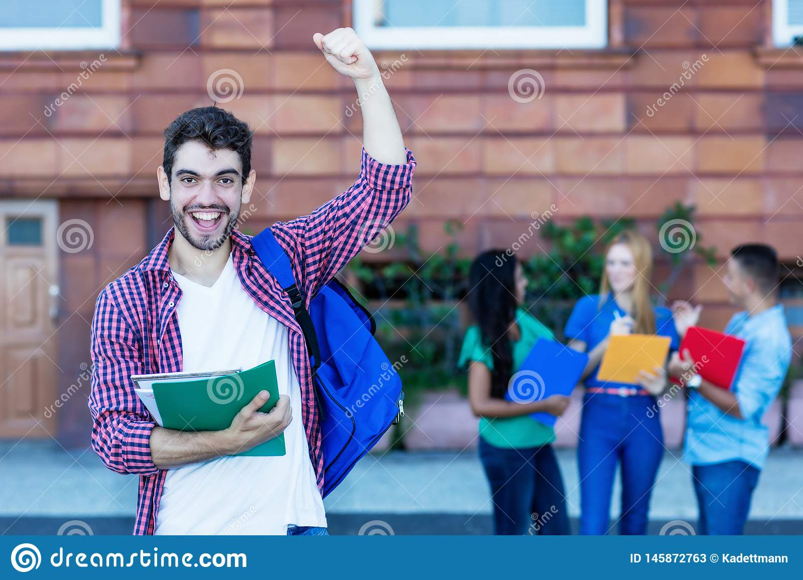Cheering spanish male student with group of students. Outdoor in the summer in the city stock photos