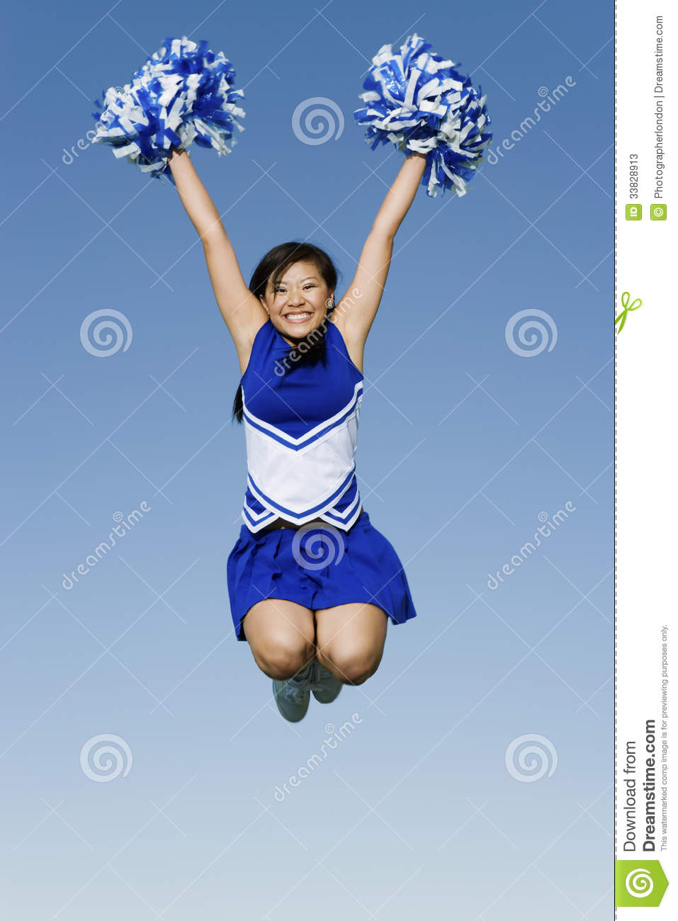 cheerleader with pompoms in midair against sky stock image