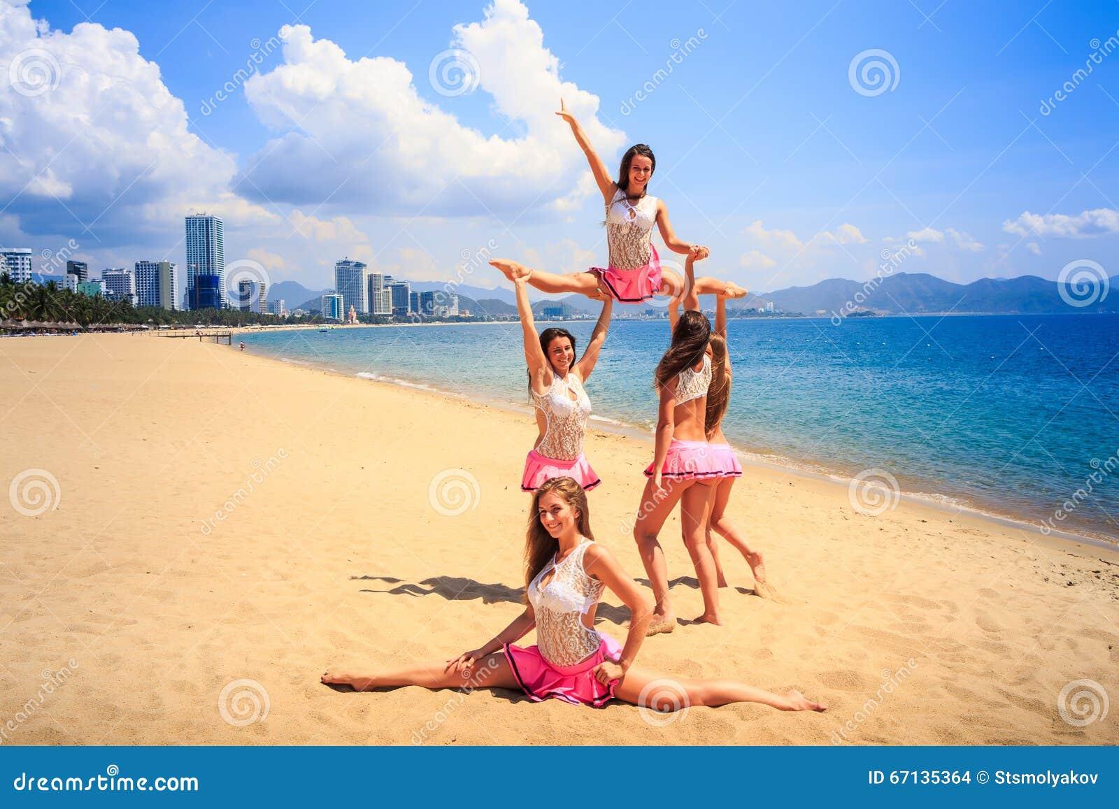 Cheerleaders perform High Straddle Stunt on beach against sea