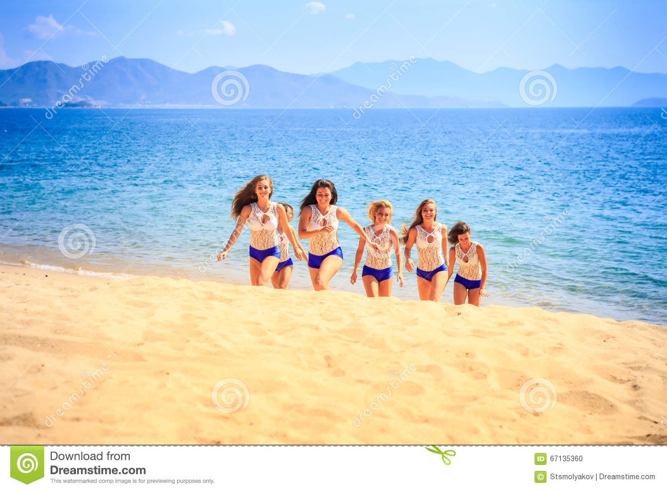 cheerleaders in white blue steps out of sea smiles on beach stock