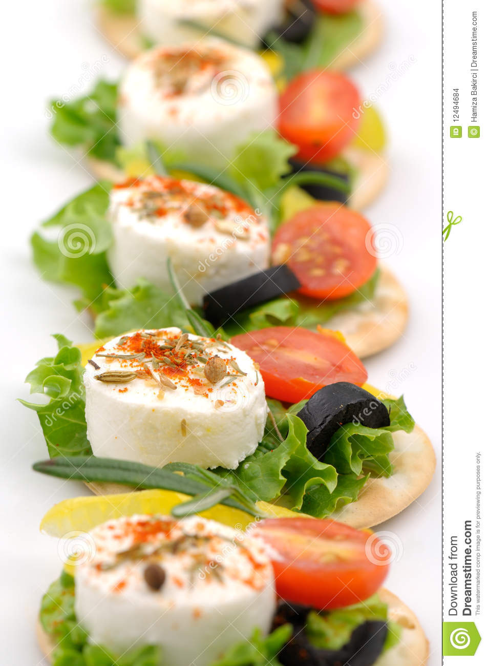 Small goat cheese slices on cracker with salad leaf, tomato, olive and ...