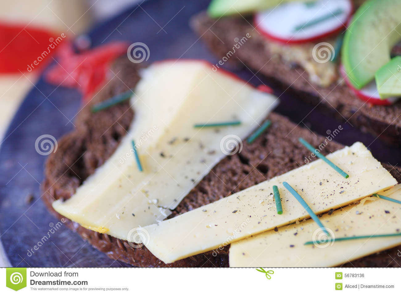 Black bread with cheese, avocado and radish, sprinkled with chives and ...