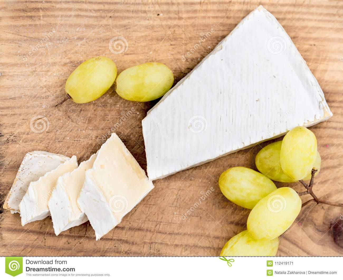 Cheese Board. Creamy Brie on rustic cutting board over white wo