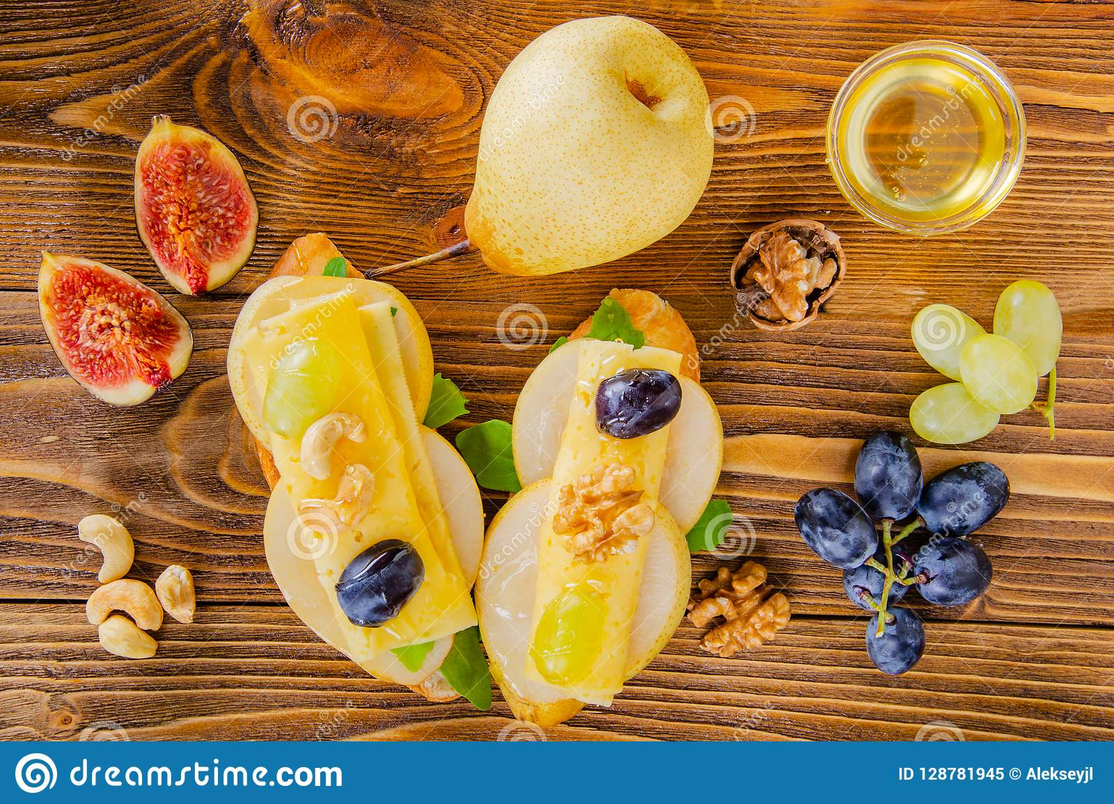 Cheese, fruit and honey. Tool for cheese. Wooden table. View fro