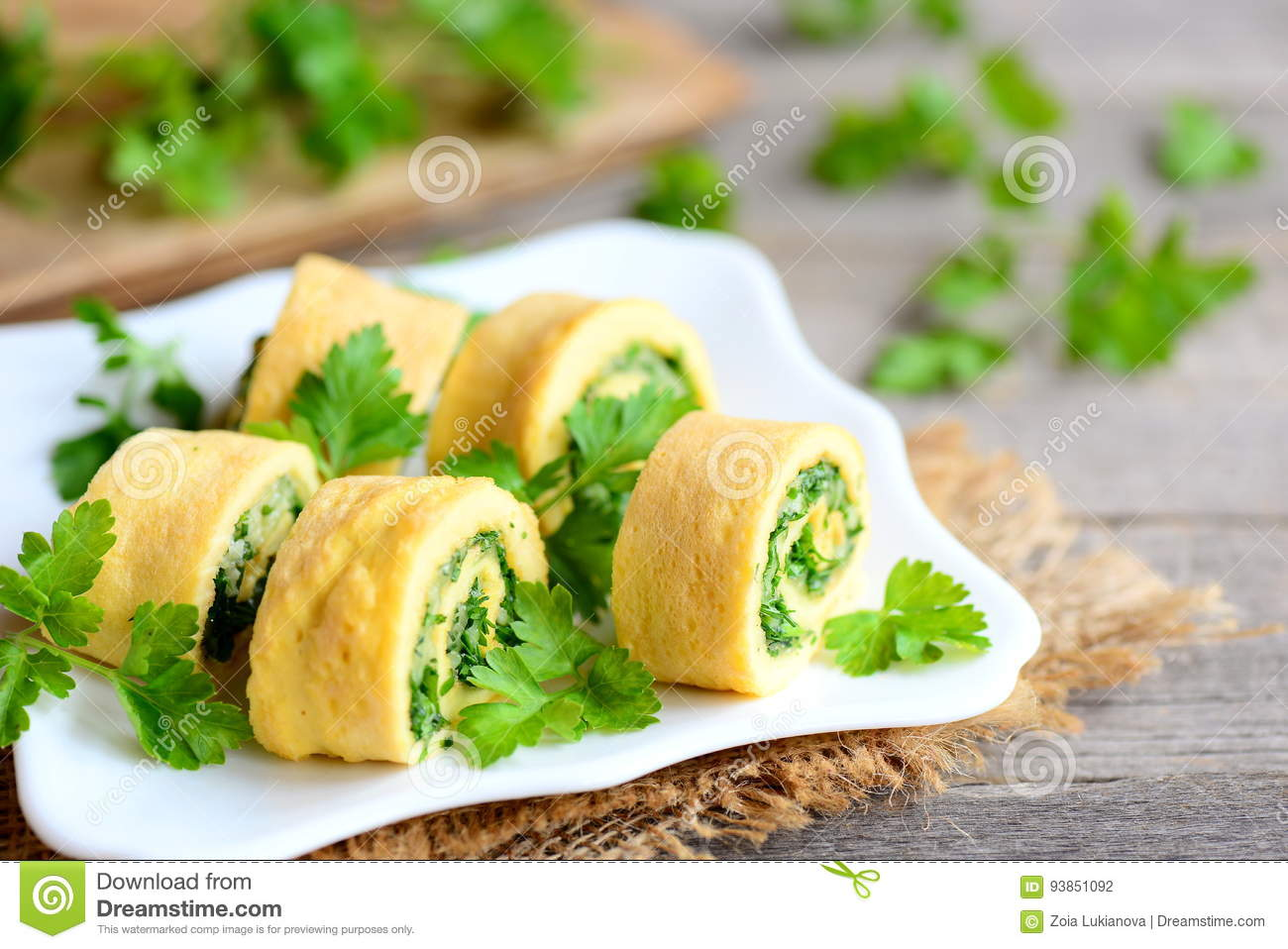 Cheese and parsley omelette rolls on a white plate. Home fried omelette rolls with grated cheese and finely chopped parsley