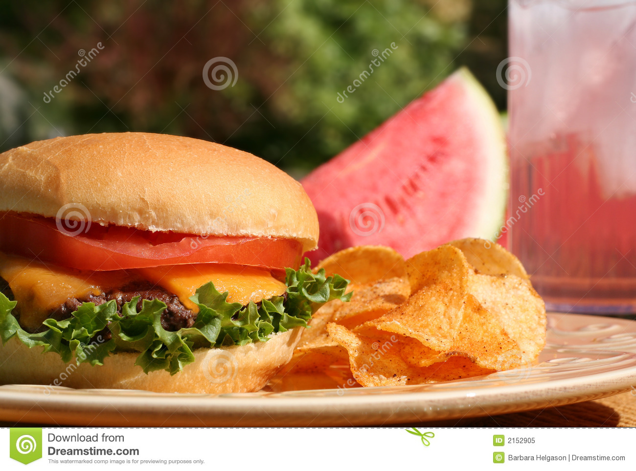 Perfect cheeseburger outside, with chips, watermelon and lemonade.