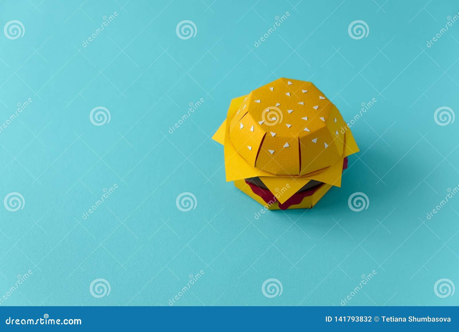 Cheeseburger de papier avec du boeuf, le fromage et la sauce sur un fond bleu Copiez l espace Concept créatif ou d art de nourrit