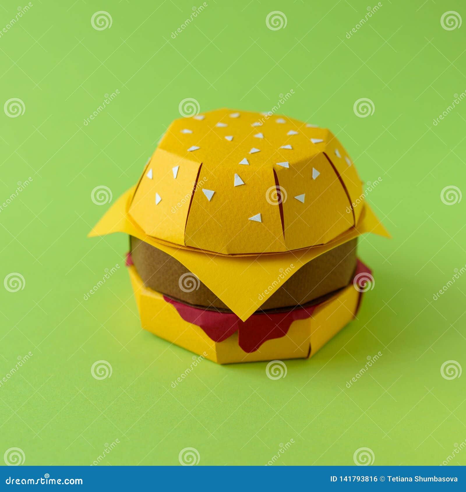 Cheeseburger de papier avec du boeuf, le fromage et la sauce sur un fond vert Copiez l espace Concept créatif ou d art de nourrit