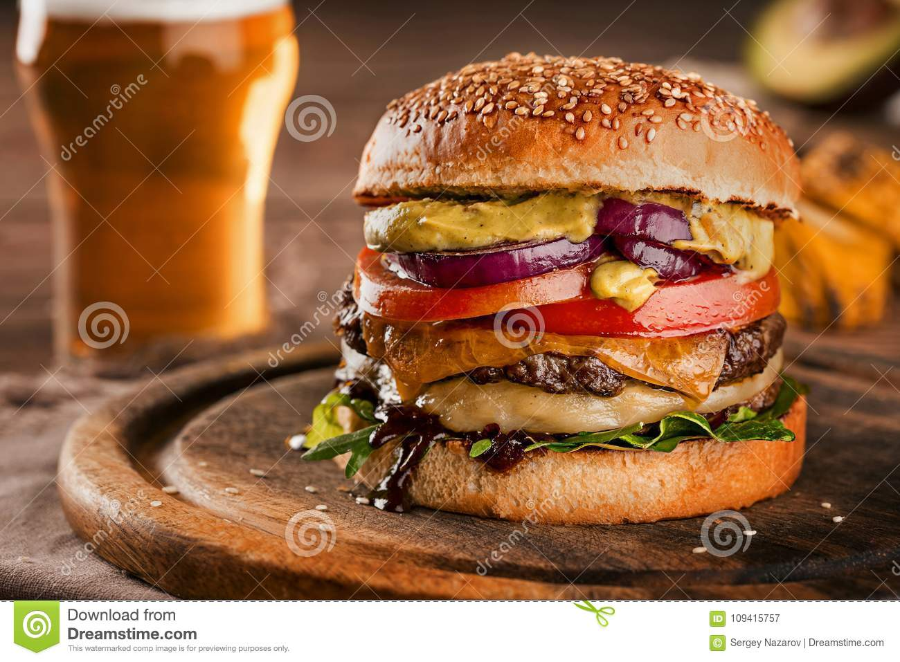 Cheeseburger, made from rye bun with tomato slice and melted cheese on a roasted beef, and lettuce leaf on a wooden
