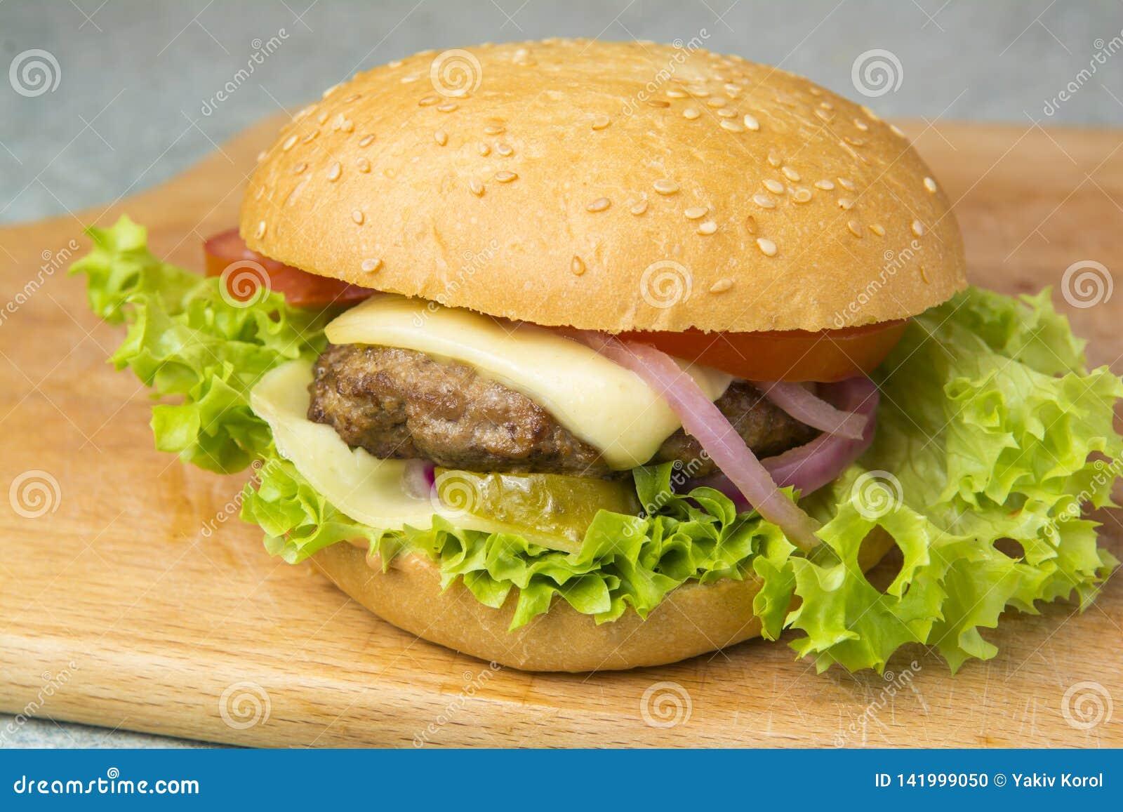 Cheeseburger z sałatą, pomidorem i cebulą na brioche babeczce,