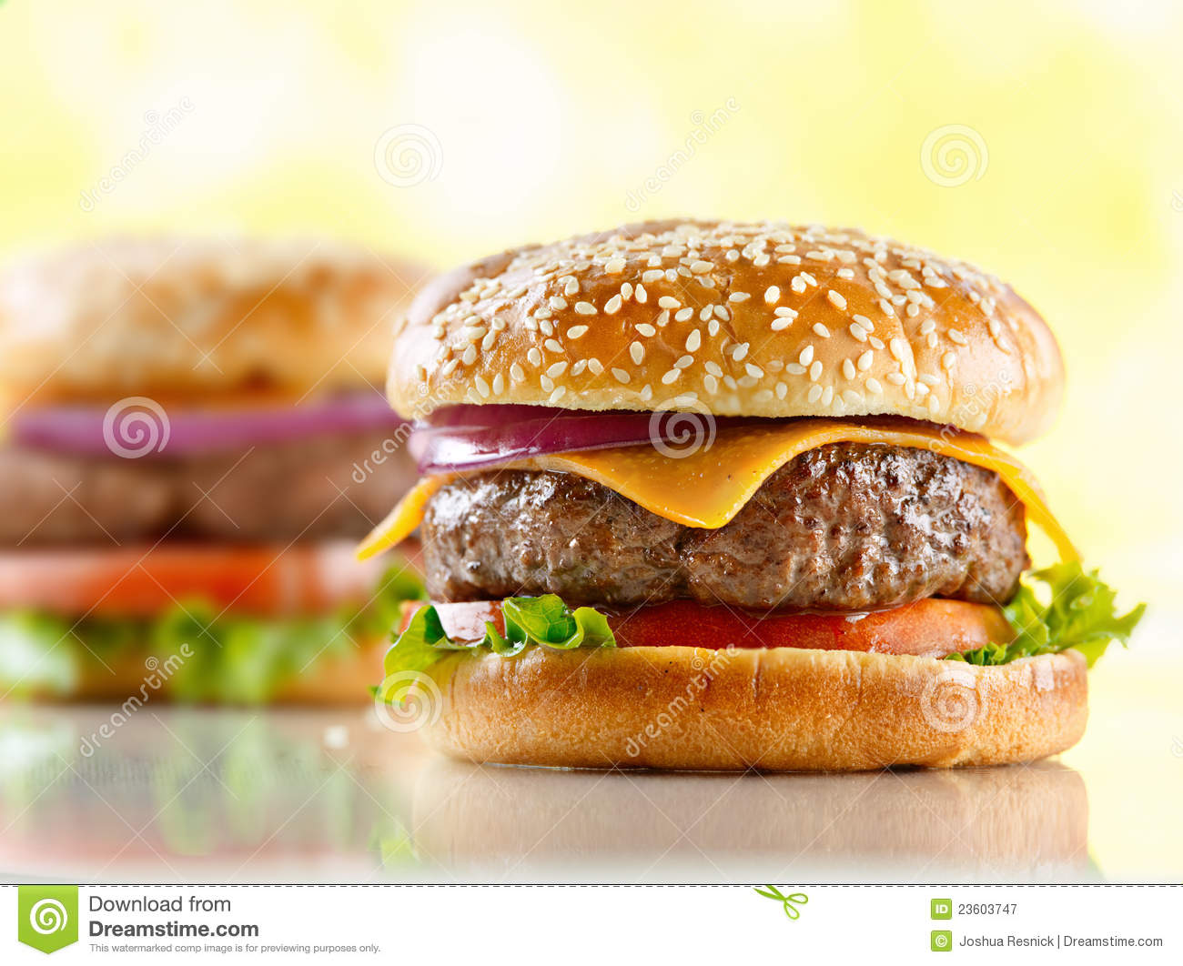 Photo of cheeseburgers with onion, lettuce, cheese and tomato on a ...