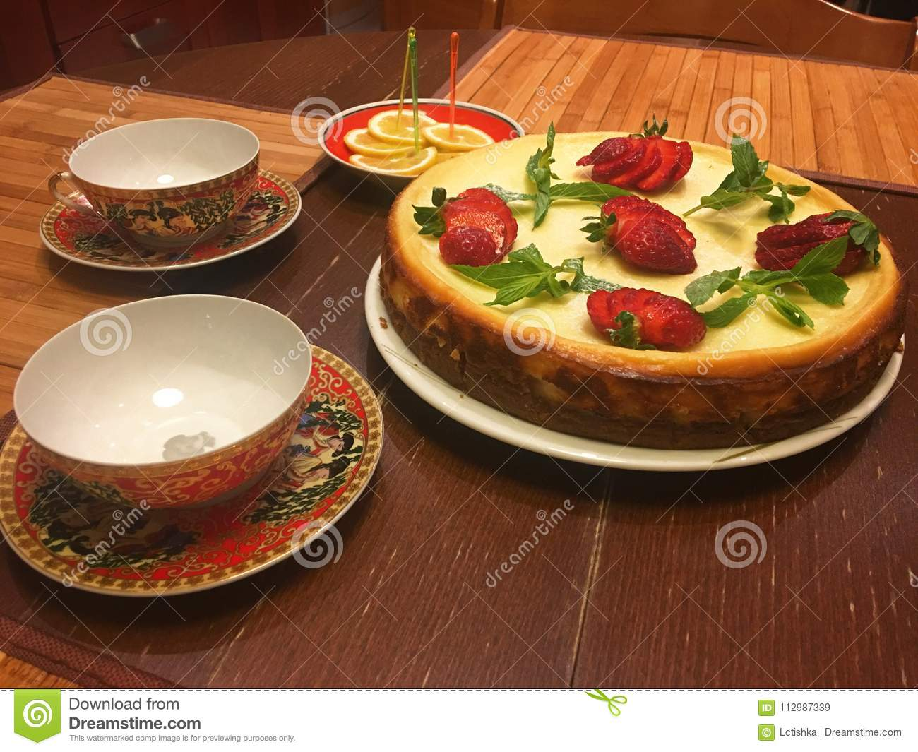 Cheesecake cake decorated with mint leaves and strawberries