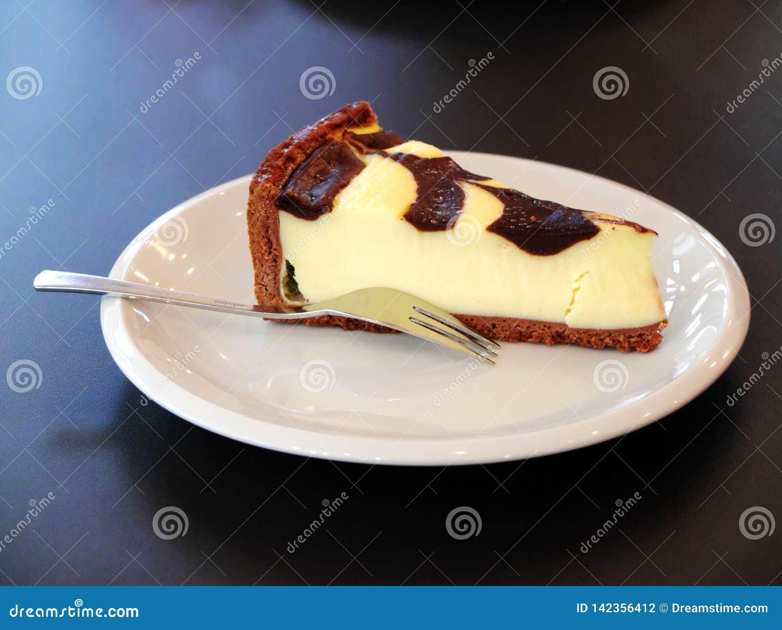 Cheesecake na bielu talerzu z rozwidleniem