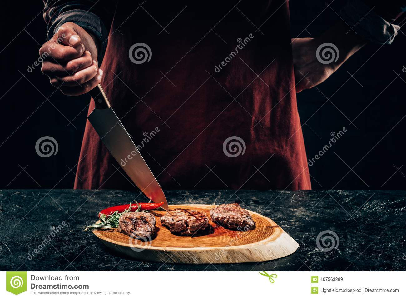 Chef in apron with meat fork and knife slicing gourmet grilled steaks with rosemary and chili pepper on wooden board