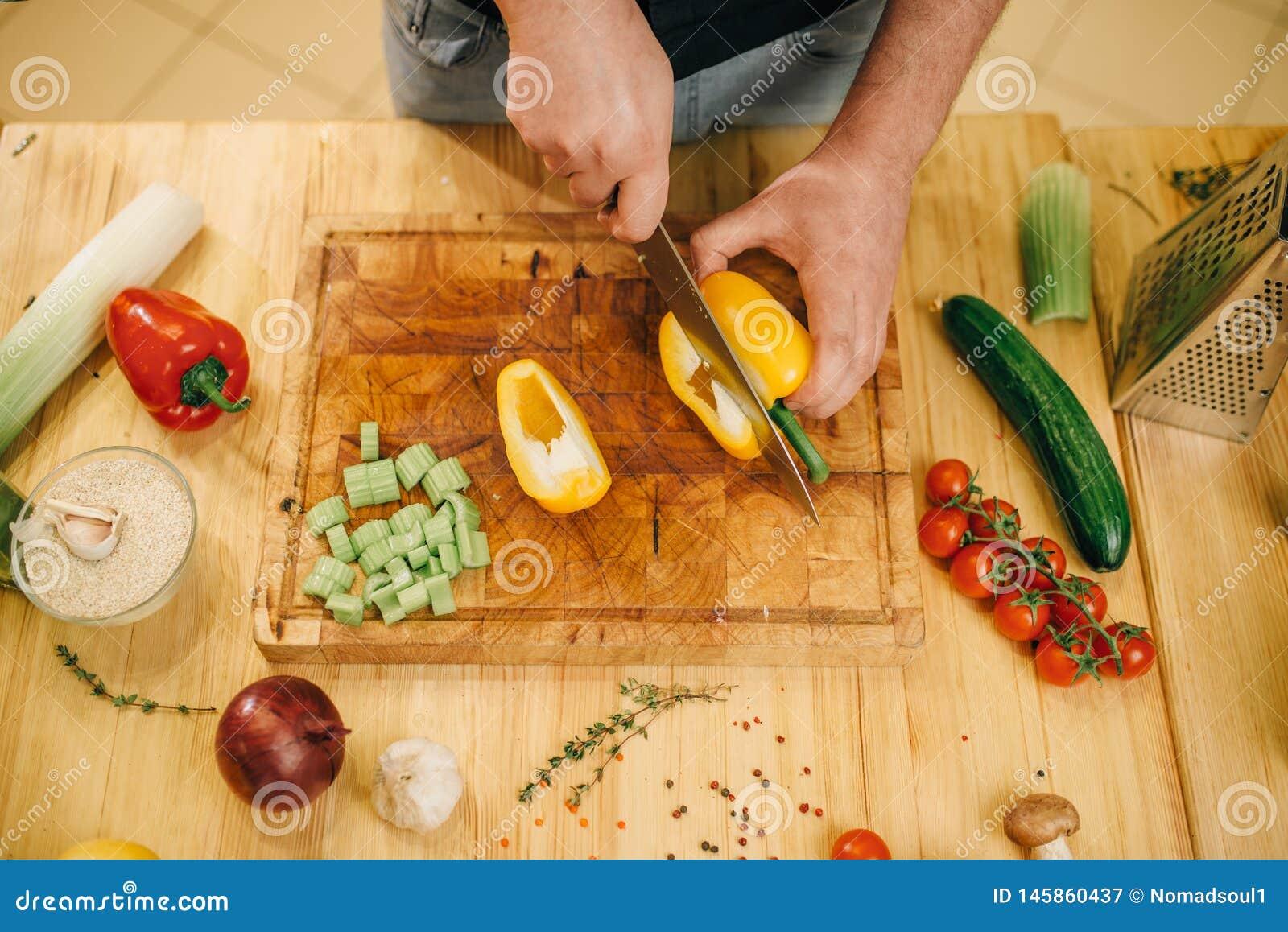 Chef avec le poivre jaune de coupes de couteau sur le conseil en bois