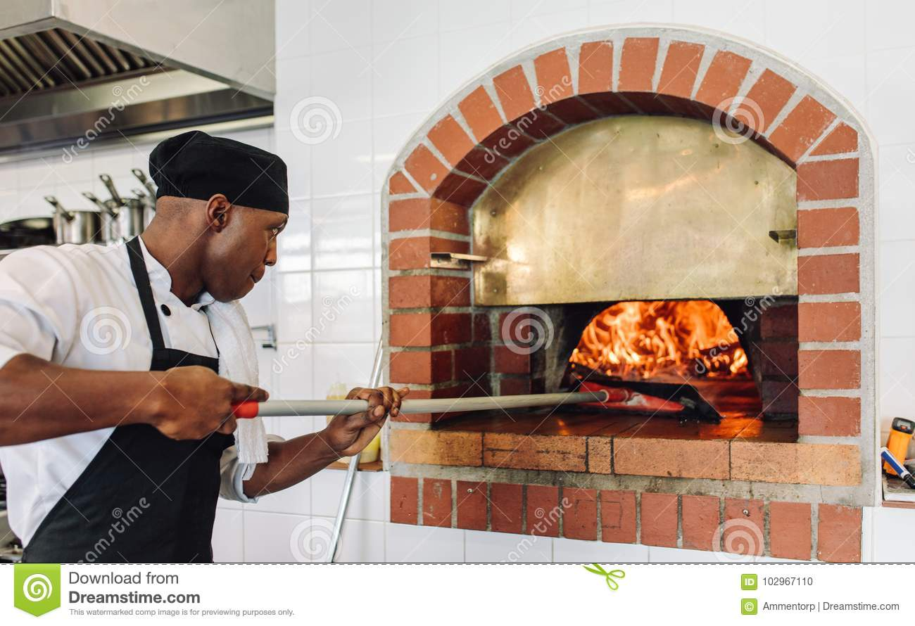 Chef baking pizza in wood fired oven