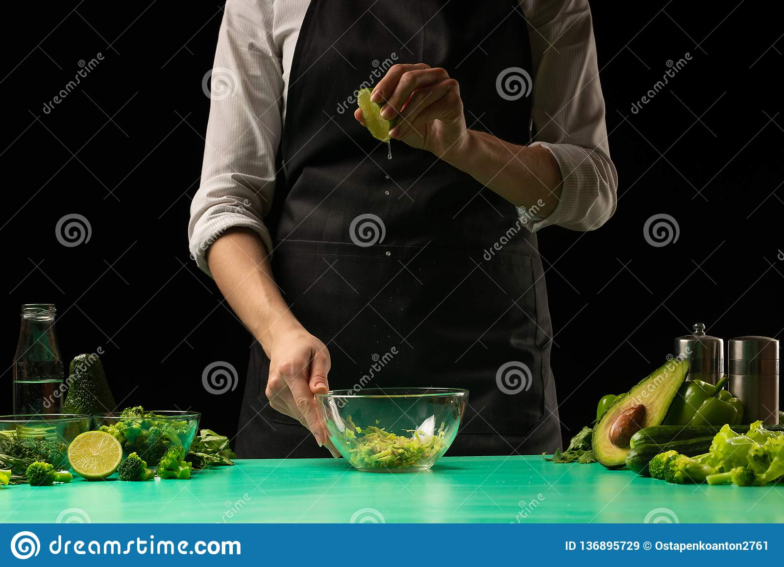 Chef on a black background pouring lime juice on vegetables for cooking cooking green detoxification smoothies. Healthy, clean