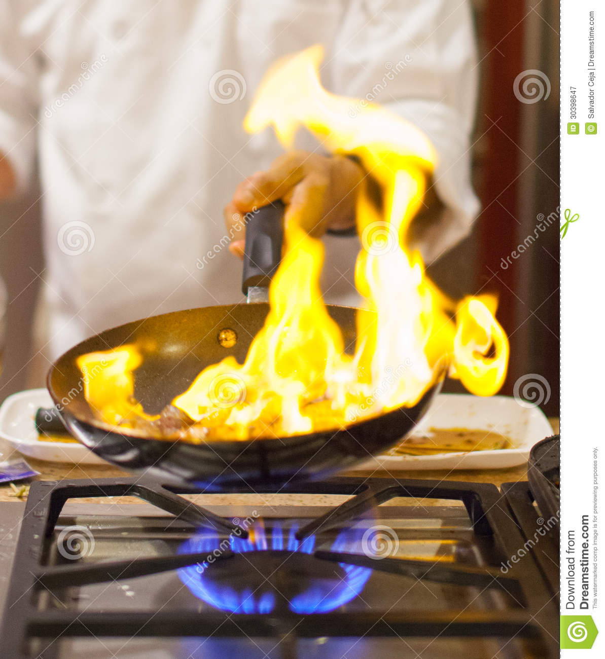 A chef cooking in the kitchen with flaming gas fire