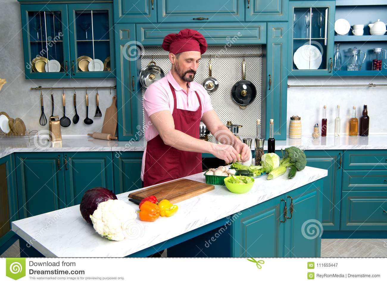 Chef cooking at kitchen. Man on kitchen cooking fresh vegetarian breakfast. Guy prepares salad with green vegetables.