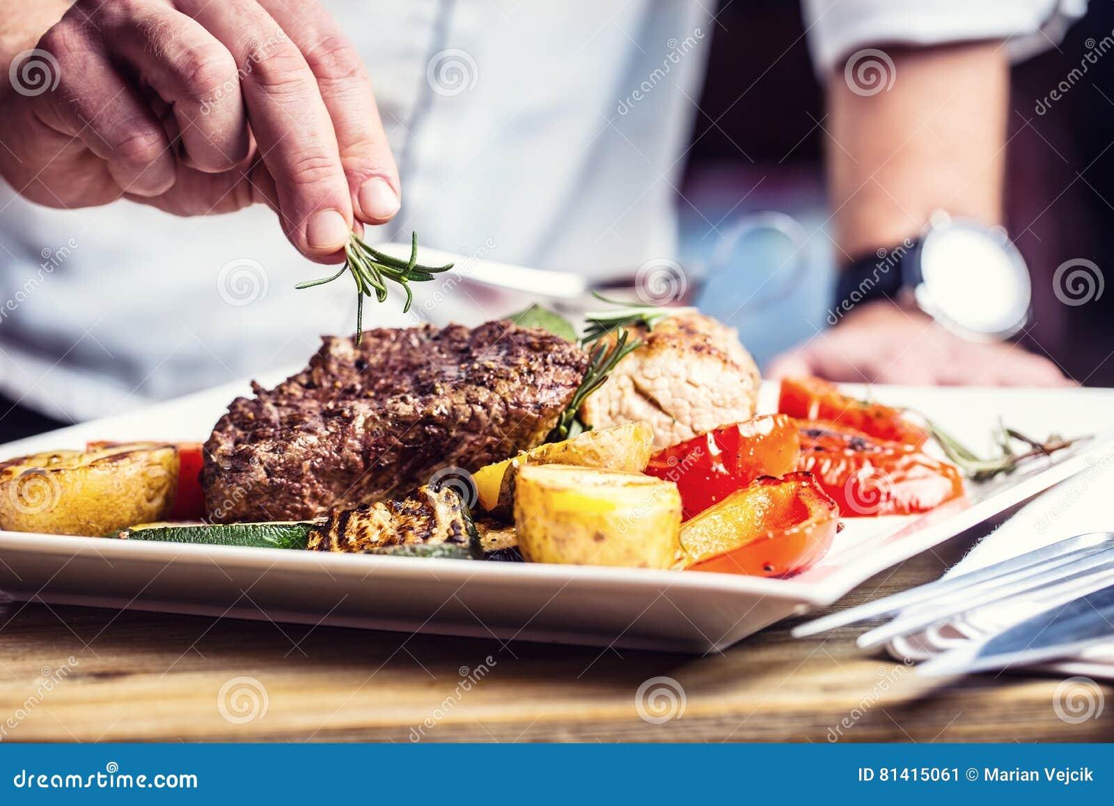 Chef dans la cuisine d hôtel ou de restaurant faisant cuire seulement des mains Bifteck de boeuf préparé avec la décoration végét