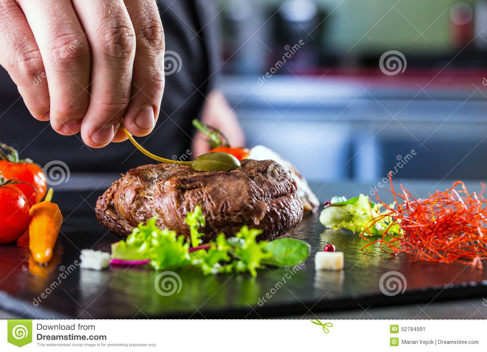 Chef dans la cuisine d hôtel ou de restaurant faisant cuire, seulement mains Bifteck de boeuf préparé avec la décoration végétale