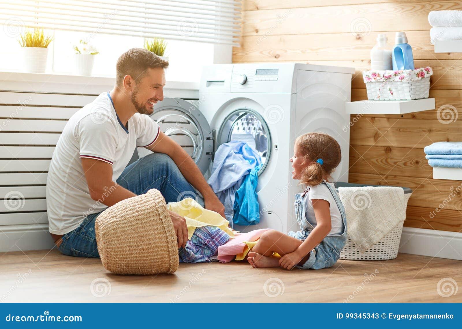 Chef de famille et enfant heureux de père de père de famille dans la blanchisserie avec