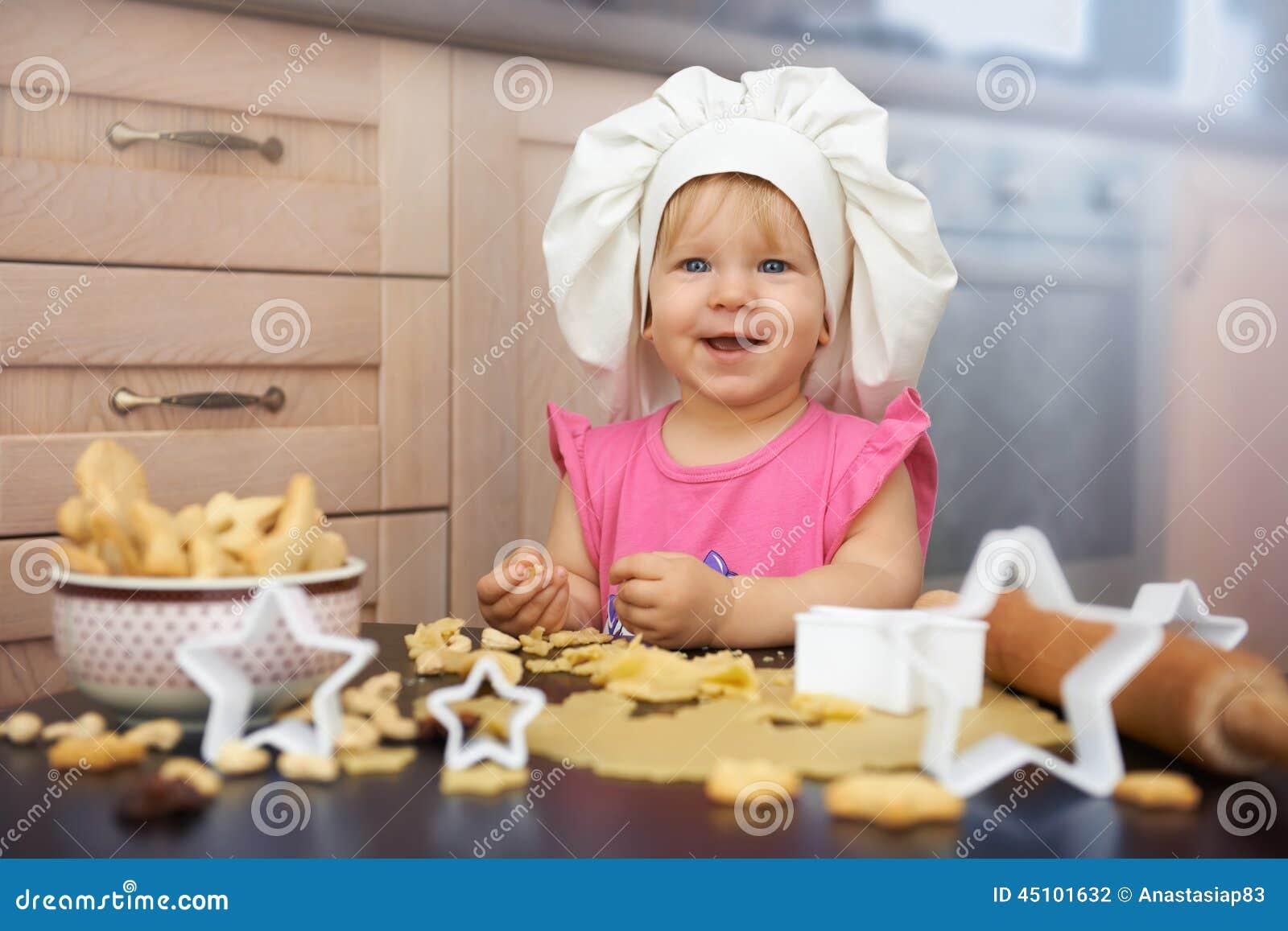 Chef de petit enfant faisant cuire des biscuits dans la cuisine