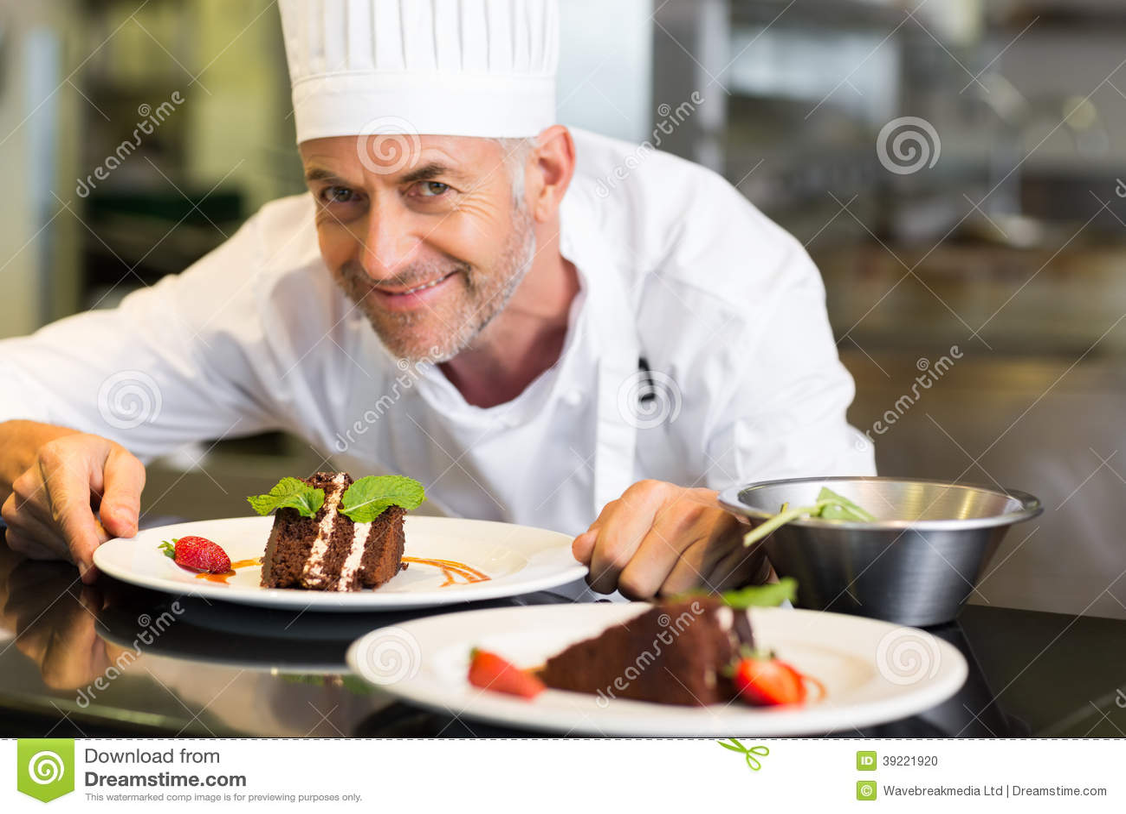 Chef De Repostería De Sexo Masculino Sonriente Con El Postre En Cocina