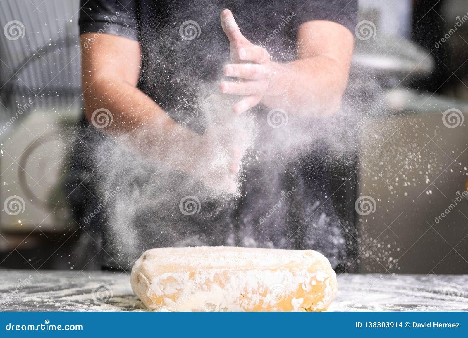 Chef de repostería que aplaude sus manos con la harina mientras que hace la pasta
