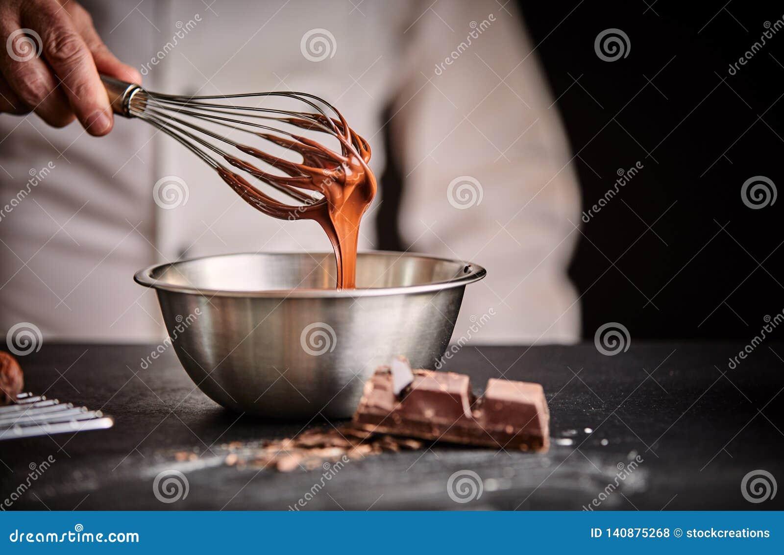 Chef, der geschmolzene Schokolade in einer Mischschüssel wischt