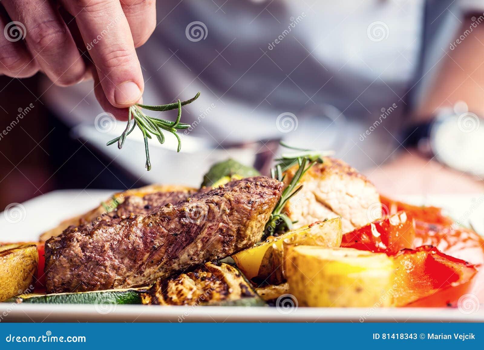 Chef in der Hotel- oder Restaurantküche nur Hände kochend Zugebereitetes Rindfleischsteak mit Gemüsedekoration