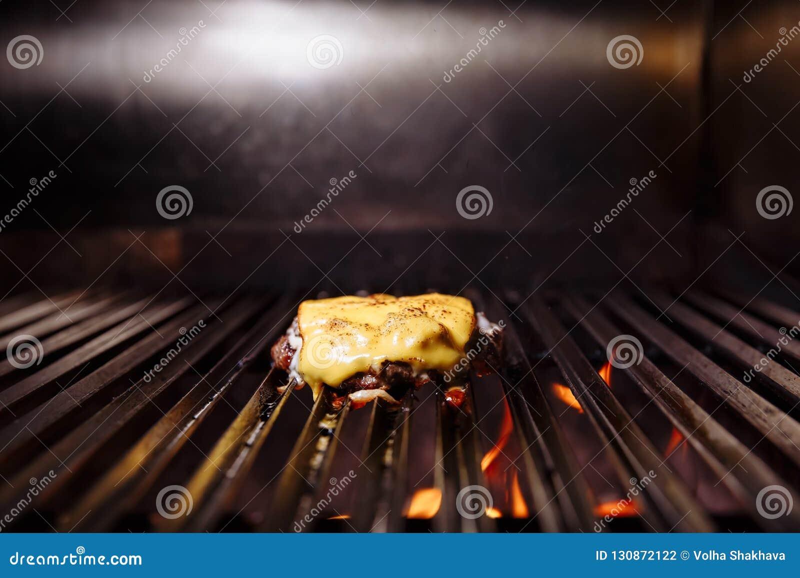 Chef faisant l hamburger Cuisson de l hamburger Côtelette de boeuf ou de porc avec du fromage grillant sur la grille