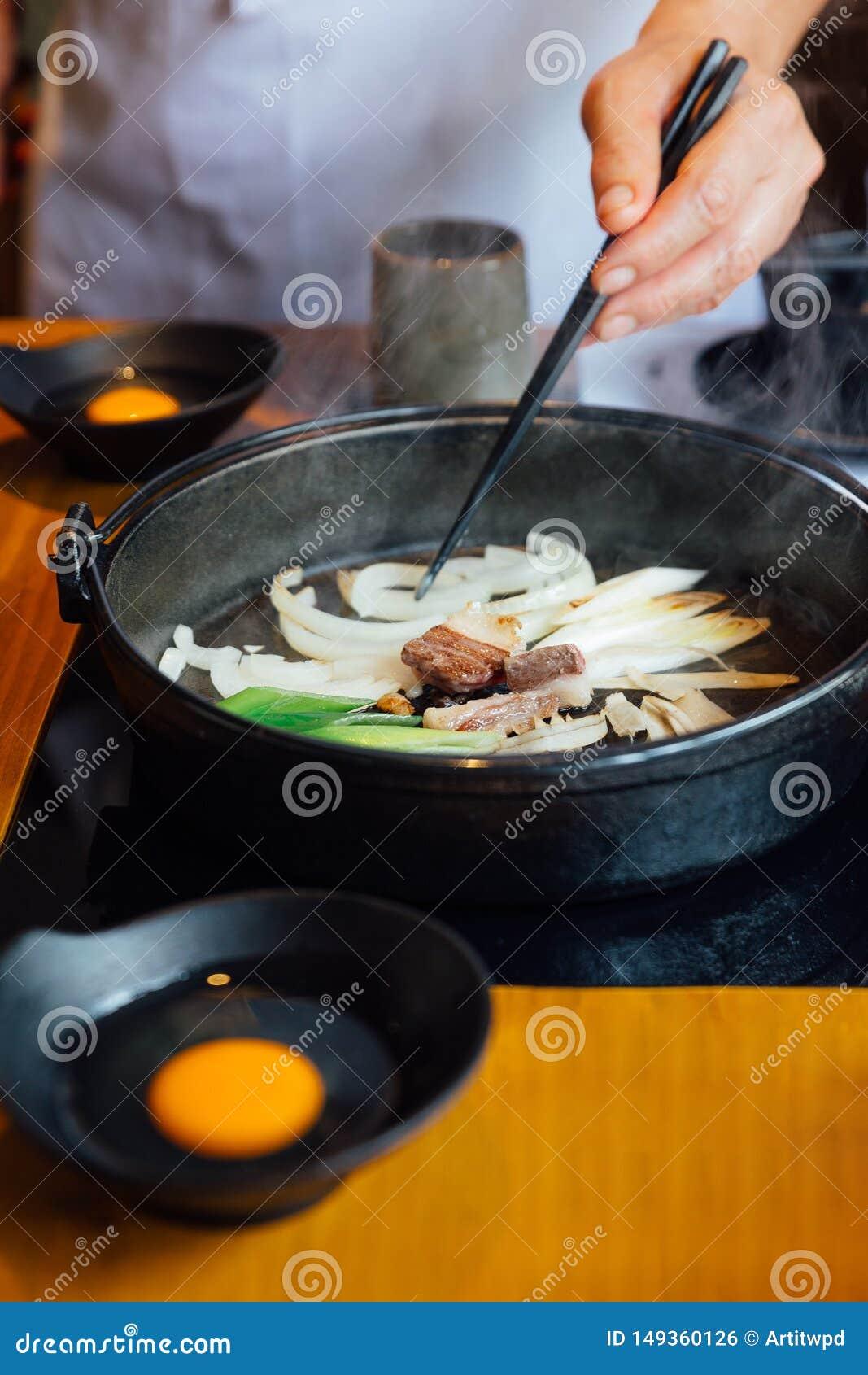 Chef gebratene Zwiebel, Schalotte und Pilz in hei?em Topf Sukiyaki, bevor Shoyu-So?ensuppe f?r das Kochen von von Wagyu Rindfleis