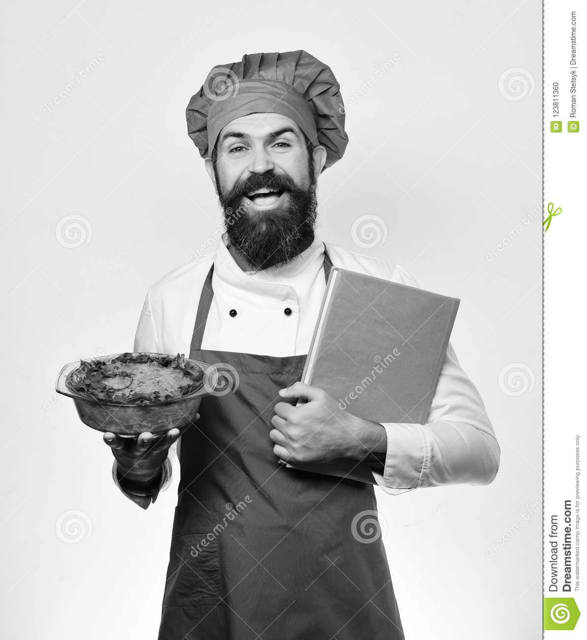 Chef holds bowl with potato casserole and price list.