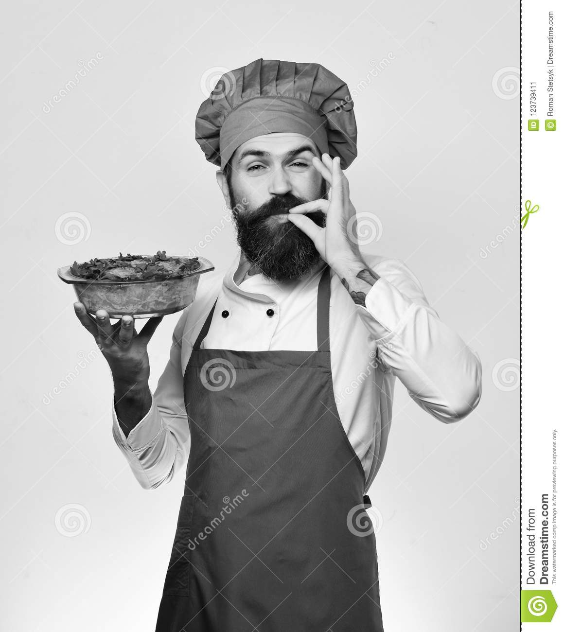 Chef holds bowl with potato casserole showing Super Tasty sign. Cook with happy face in burgundy uniform holds baked