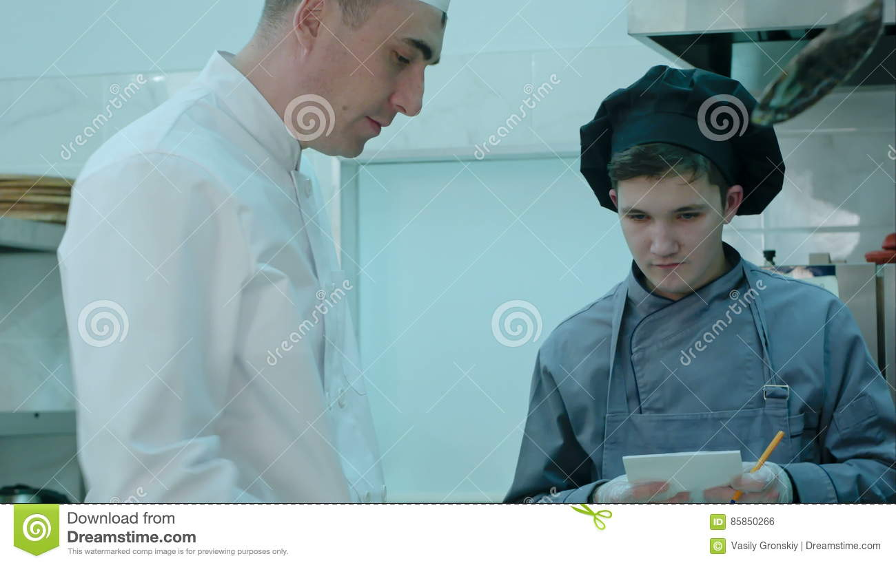 Chef Instructing Trainee In The Kitchen While He Is Taking Notes ...