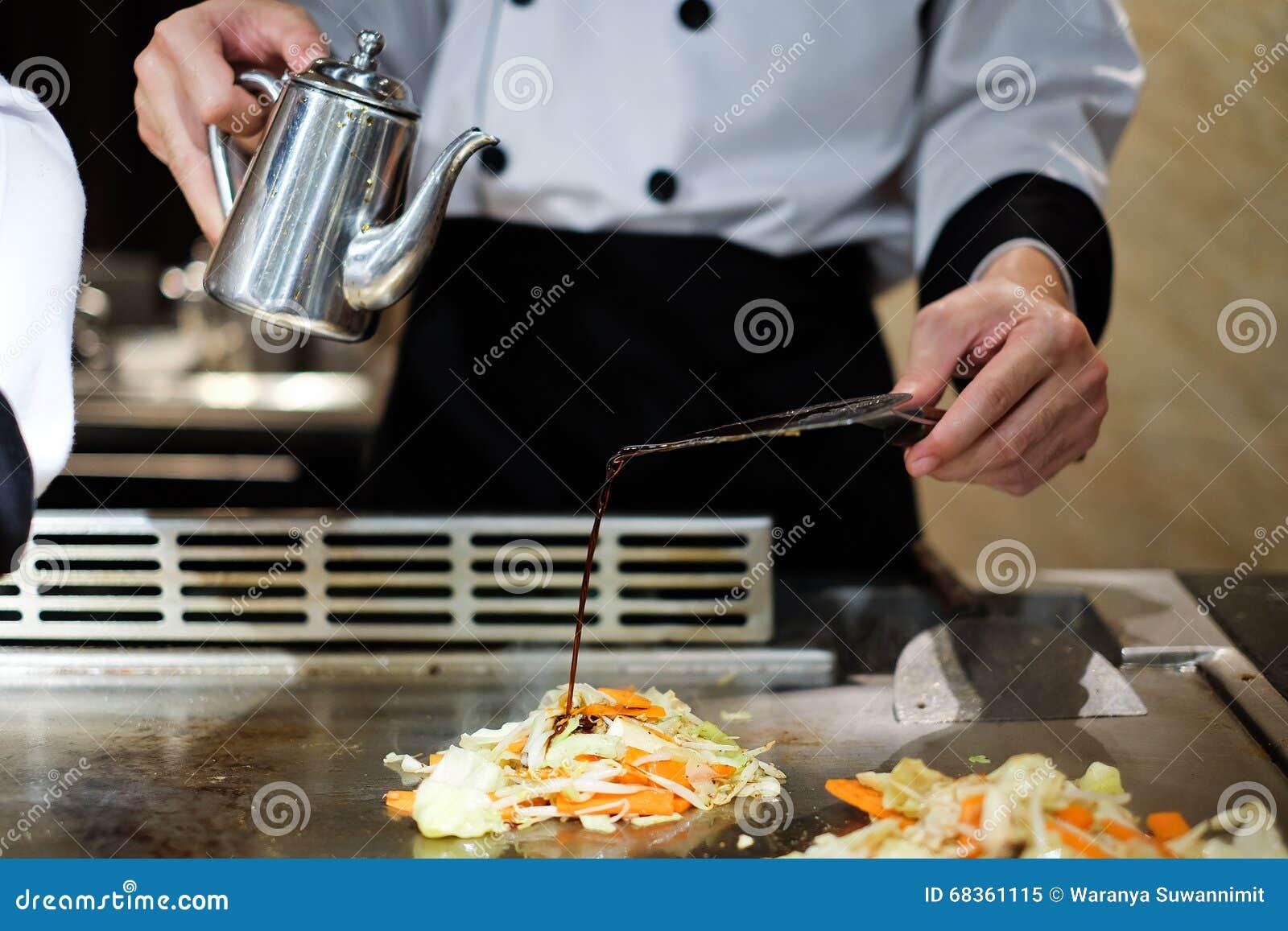 Chef japonais délibérément préparant et faisant cuire le teppanyaki traditionnel de boeuf